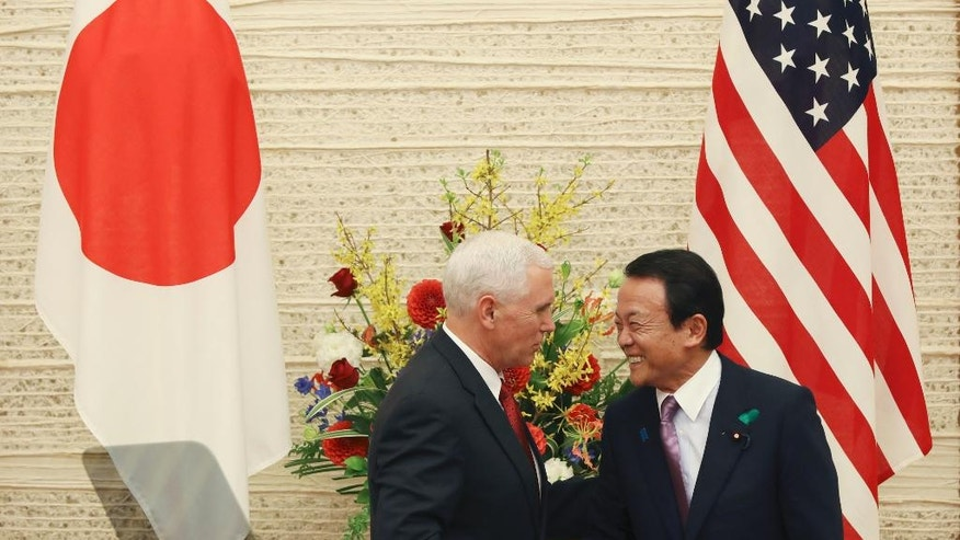 "U.S. Vice President Mike Pence, left, and Japanese Deputy Prime Minister and Finance Minister Taro Aso shake hands as they end the joint press conference at the prime minister's office in Tokyo, Tuesday, April 18, 2017. After meeting with Japanese Prime Minister Shinzo Abe, Pence held talks with Aso on a new U.S.-Japan ""economic dialogue"" to be led by the two. The new forum for trade talks was launched by U.S. President Donald Trump and Abe during the Japanese leader's visit to the U.S. in February. (AP Photo/Eugene Hoshiko)"