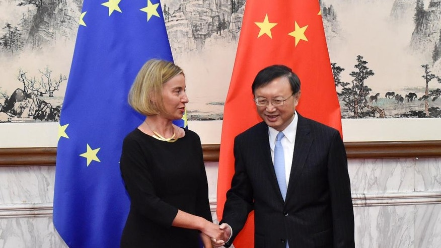 Federica Mogherini, left, high representative of the European Union for Foreign Affairs and Security Policy, shakes hands with Chinese State Councilor Yang Jiechi before their meeting at Diaoyutai State Guesthouse in Beijing, Wednesday, April 19, 2017. (Kenzaburo Fukuhara/Pool Photo via AP)