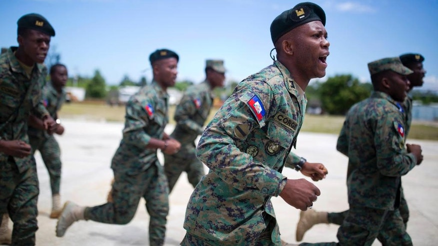 In this April 11, 2017 photo, members of Haiti's new national military force run and chant during training at a former U.N. base in Gressier, Haiti. As U.N. military peacekeepers prepare for a full exit from this Caribbean nation, Haiti is trying to revive a military force 22 years after a national army was disbanded. (AP Photo/Dieu Nalio Chery)