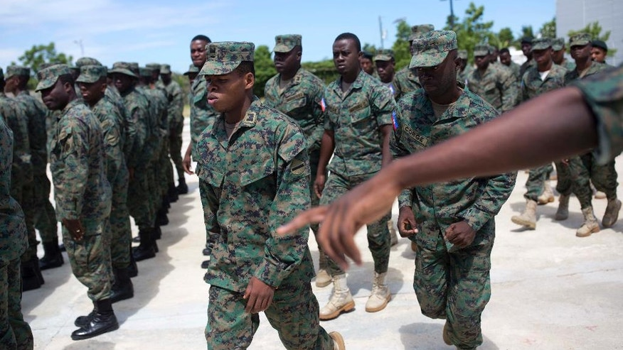 In this April 11, 2017 photo, Lt. B. Jean Judney, a member of Haiti's new national military force points directions to his soldiers during training at a former U.N. base in Gressier, Haiti. While Haiti is a long way off from having a real military, efforts to build up a defense force at whatever level excites some and unnerves others. (AP Photo/Dieu Nalio Chery)
