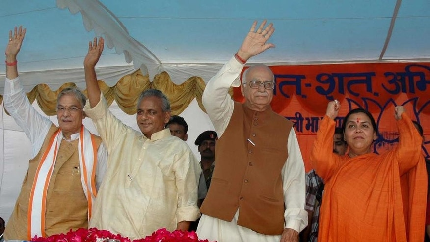 FILE - In this July 28, 2005 file photo, Indian opposition leader and President of the Bharatiya Janta Party (BJP) L.K. Advani, second right, senior BJP leaders Uma Bharati, right, Kalyan Singh, second left, and Murli Manohar Joshi wave to people during a public rally in Rae Bareilly, in the northern Indian state of Uttar Pradesh. India's top court said Wednesday, April 19, 2017, that the four senior leaders of India's ruling Hindu nationalist Bharatiya Janata Party will stand trial for their role in a criminal conspiracy over the destruction of the 16th century Babri mosque in 1992, an event that sparked bloody nationwide rioting. Of the four main leaders who will now stand trial, Singh is currently the governor of an Indian province, and the constitution protects him from criminal trial. Therefore his trial will start after his term ends. (AP Photo/Rajesh Kumar Singh, File)