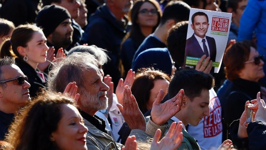 Supporters with a leaflet of French Socialist presidential candidate Benoit Hamon applause during a last-ditch rally and concert in Paris, Wednesday, April 19, 2017. Hamon is polling a distant fifth place ahead of Sunday's first-round election and has little chance of reaching the decisive May 7 runoff. (AP Photo/Francois Mori)