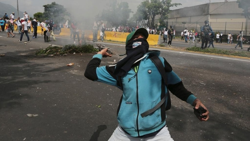 "A demonstrator throws stones during anti-government protests in Caracas, Venezuela, Wednesday, April 19, 2017. Tens of thousands of opponents of President Nicolas Maduro flooded the streets of Caracas in what's been dubbed the ""mother of all marches"" against the embattled president. (AP Photo/Fernando Llano)"