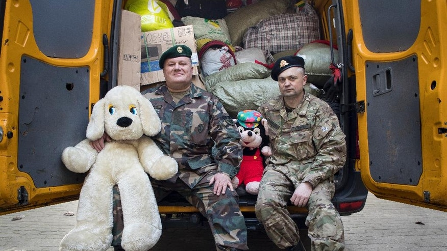 Charity and Support Foundation volunteers Algis Simoniutis, right,  and Audrius Brazauskas pose with toys before loading  them into a van to send them to eastern Ukraine from Vilnius, Lithuania, Tuesday, March 28, 2017. (AP Photo/Mindaugas Kulbis)