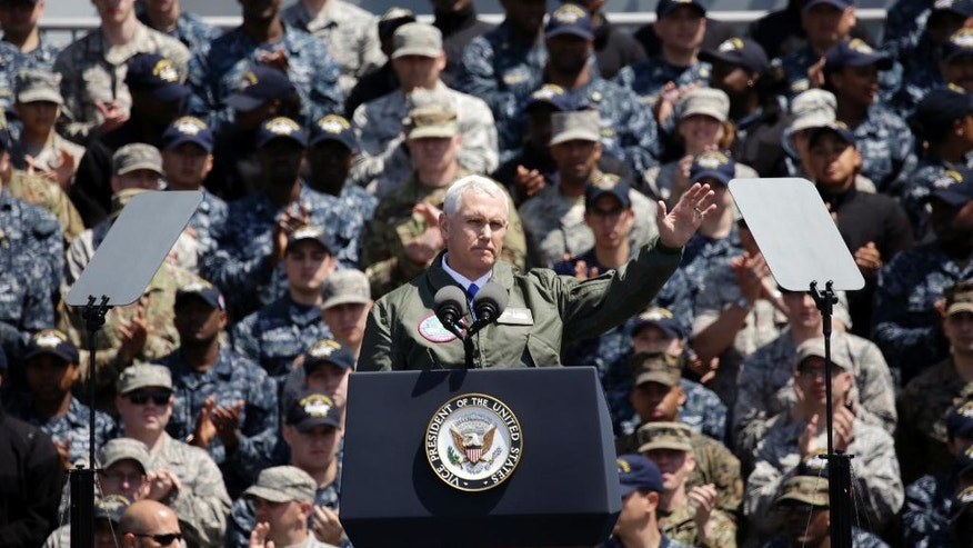 U.S. Vice President Mike Pence, front, waves to U.S. servicemen and Japanese Self-Defense Forces personnel on the flight deck of U.S. navy nuclear-powered aircraft carrier USS Ronald Reagan, at the U.S. Navy's Yokosuka base in Yokosuka, south of Tokyo, Wednesday, April 19, 2017. (AP Photo/Eugene Hoshiko)