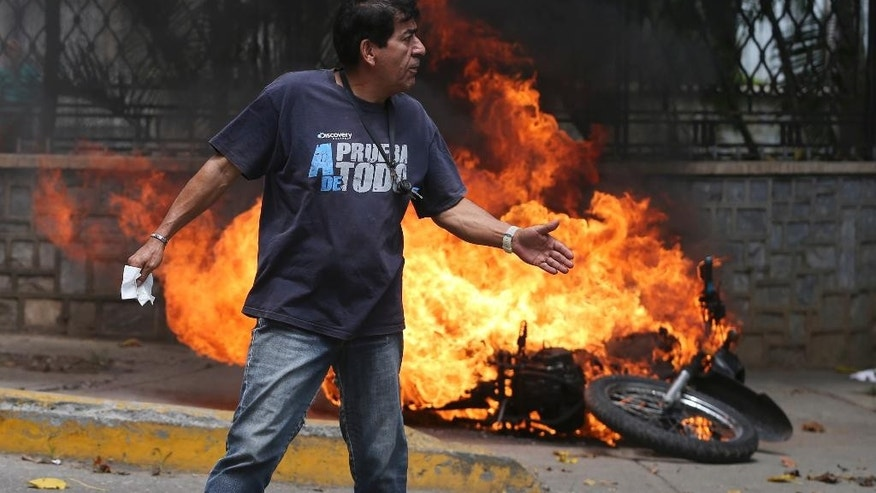 "A man walks past a burning motorbike set on fire by protesters during an opposition march in Caracas, Venezuela, Wednesday, April 19, 2017. Opponents of President Nicolas Maduro called on Venezuelans to take to the streets on Wednesday for what they dubbed the ""mother of all marches"" against the embattled socialist leader. Government supporters are holding their own counter demonstration. (AP Photo/Fernando Llano)"