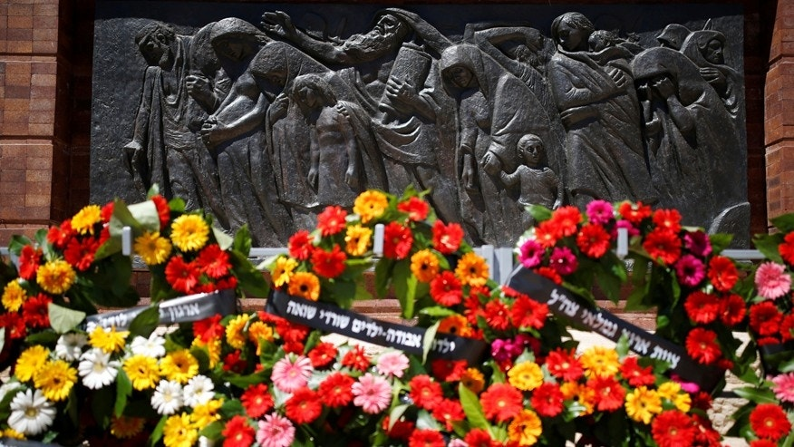 Wreaths are seen next to a sculpture during a ceremony marking Holocaust Remembrance Day at Warsaw Ghetto Square at Yad Vashem Holocaust memorial in Jerusalem May 5, 2016. REUTERS/Amir Cohen  - RTX2CY0L