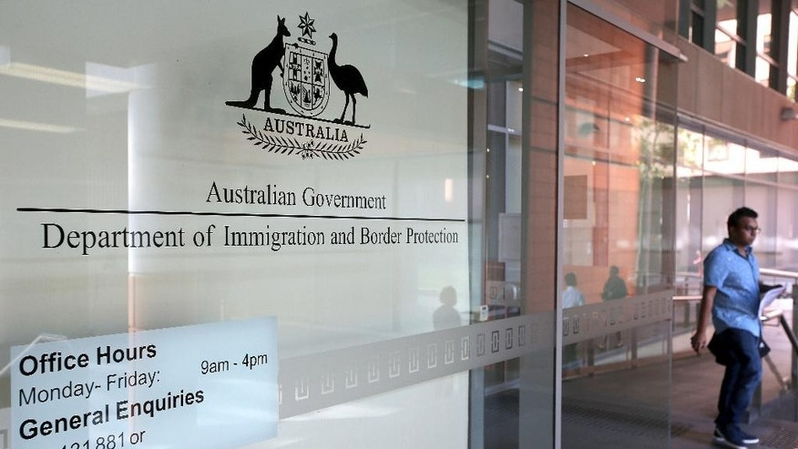 A man leaves the Department of Immigration and Border Protection offices in Sydney, Thursday, April 20, 2017. Australia plans to tighten its citizenship rules to require higher English language skills, longer residency and evidence of integration such as a job. (AP Photo/Rick Rycroft)