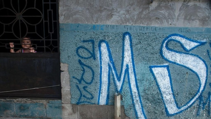 FILE - In this June 21, 2016 file photo, a child peers from behind the door of her home, covered with Mara Salvatrucha gang graffiti, in Soyapango, El Salvador. Attorneys general in Central America are expressing concern on Thursday, April 20, 2017 over comments from their U.S. counterpart suggesting increased deportations of gang members by the United States. (AP Photo/Salvador Melendez, File)