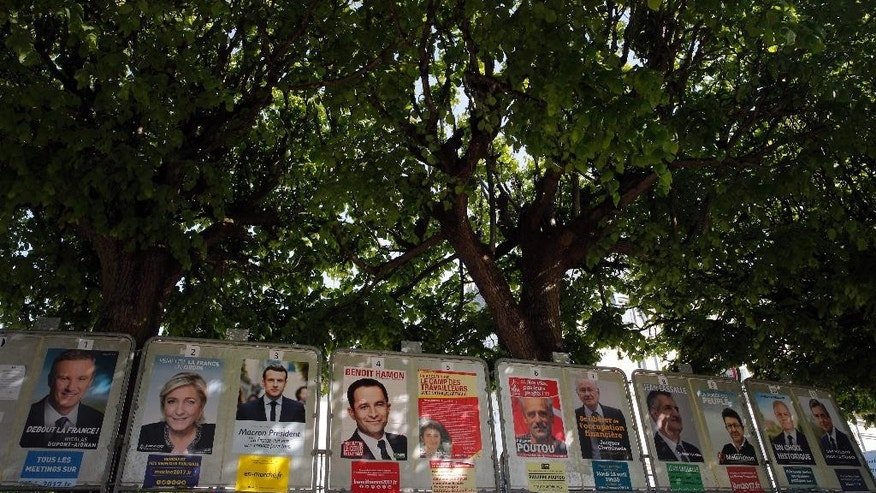 French presidential campaign posters are displayed in Marnes-la-Coquette, outside Paris, Thursday, April 20, 2017. The two-round presidential election is set for April 23 and May 7. (AP Photo/Christophe Ena)