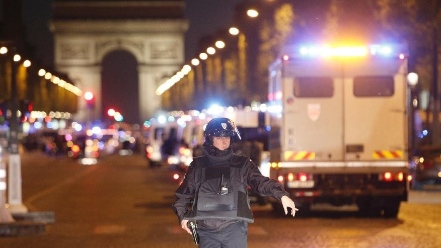 A police officer stands guard after a fatal shooting in which a police officer was killed along with an attacker on the Champs Elysees in Paris, France, Thursday, April 20, 2017. French media are reporting that two police officers were shot Thursday on the famed shopping boulevard. Many police vehicles can be seen on the avenue that passes many of the city's most iconic landmarks. (AP Photo/Thibault Camus)