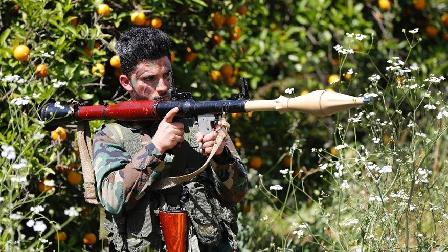 A Hezbollah fighter holds an RPG as he takes his position between orange trees, at the coastal border town of Naqoura, south Lebanon, Thursday, April 20, 2017. Hezbollah organized a media tour along the border with Israel meant to provide an insight into defensive measures established by the Israeli forces along the southern frontier in the past year in preparation for any future conflict. (AP Photo/Hussein Malla)