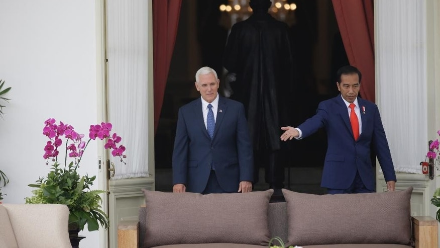 U.S. Vice President Mike Pence, left, is shown the way by Indonesian President Joko Widodo during their meeting at Merdeka Palace in Jakarta, Indonesia, Thursday, April 20, 2017. Pence is currently on a 10-day trip in Asia. (AP Photo/Dita Alangkara, Pool)