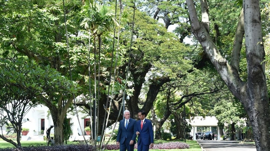 U.S. Vice President Mike Pence, left, walks in the garden of Merdeka Palace with Indonesian President Joko Widodo during their meeting in Jakarta, Indonesia, Thursday, April 20, 2017. Indonesia is the latest stop on an Asian tour by Pence that is reinforcing traditional U.S. alliances at a time when Donald Trump's presidency has raised questions about the strength of the U.S. commitment to the region. (Bay Ismoyo/Pool Photo via AP)