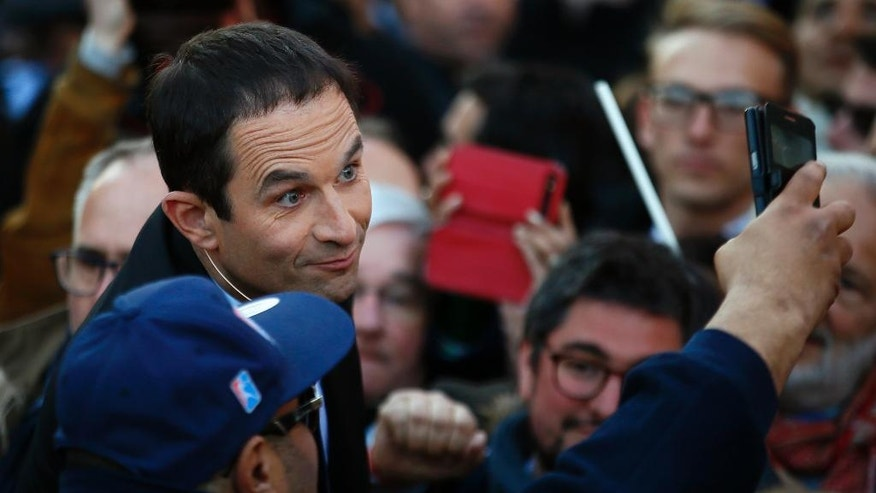 French Socialist presidential candidate Benoit Hamon, left, poses for a selfie with supporters during a last-ditch rally and concert in Paris, Wednesday, April 19, 2017. Hamon is polling a distant fifth place ahead of Sunday's first-round election and has little chance of reaching the decisive May 7 runoff. (AP Photo/Francois Mori)