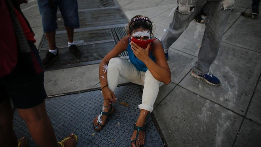 "A demonstrator sits on the street overcome by tear gas during anti-government protests in Caracas, Venezuela, Wednesday, April 19, 2017. Tens of thousands of opponents of President Nicolas Maduro flooded the streets of Caracas in what's been dubbed the ""mother of all marches"" against the embattled socialist president. (AP Photo/Ariana Cubillos)"