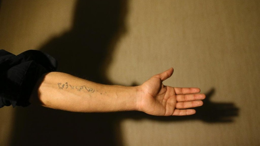 "In this March 21, 2017 photograph, Mohammmed, last name not given, shows a tattoo on his forearm that reads in Arabic: ""All for you, mother"", during an interview with The Associated Press, in Gaziantep, southeastern Turkey. He was barely 20 when Islamic State group militants stormed his home city of Deir el-Zour in the oil-rich east of Syria. Mohammed had already been fighting government forces the past two years, so it was an easy decision for him: Join the militants to keep up the battle against President Bashar Assad's rule. (AP Photo/Lefteris Pitarakis)"