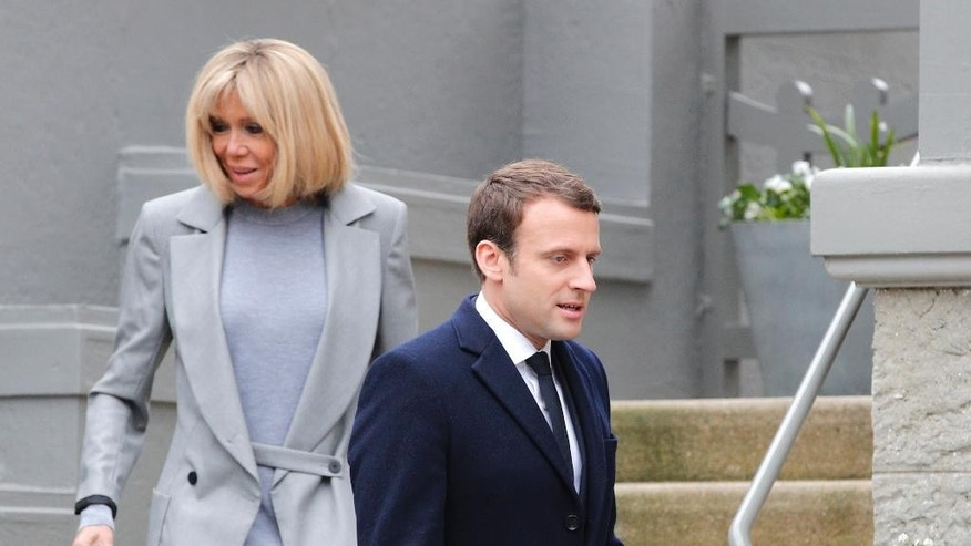 Centrist candidate Emmanuel Macron and his wife Brigitte leave their house before voting in the first round of the French presidential election, in le Touquet, northern France, Sunday April 23, 2017. (AP Photo/Christophe Ena)