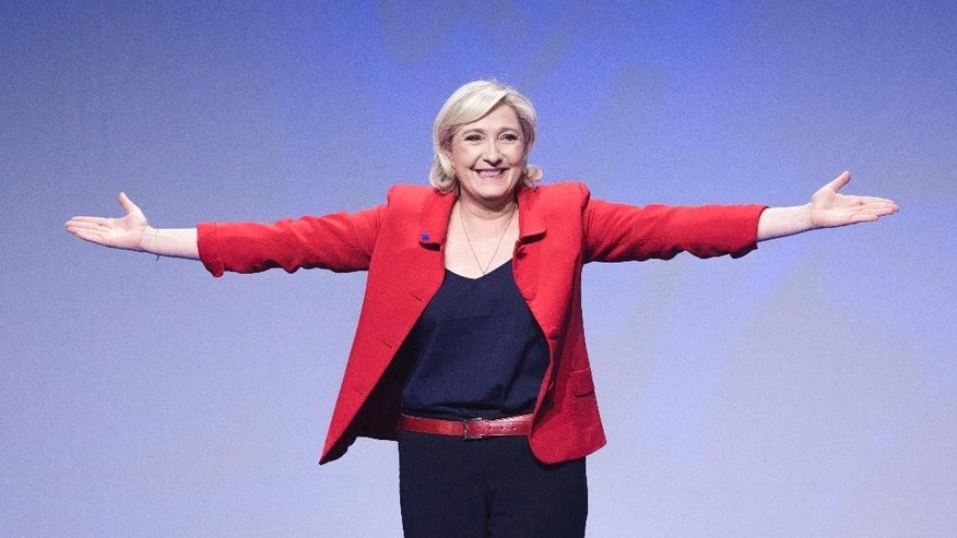 FILE - In this April 17, 2017 file photo, far-right candidate for the presidential election Marine Le Pen gestures as she arrives for a campaign meeting in Paris. Marine Le Pen, whose passion for politics and far-right values were forged in the cradle, is making her second bid for the French presidency, hoping this time to break through the ceiling of fear that stopped her father from winning in 2002. (AP Photo/Kamil Zihnioglu, File)