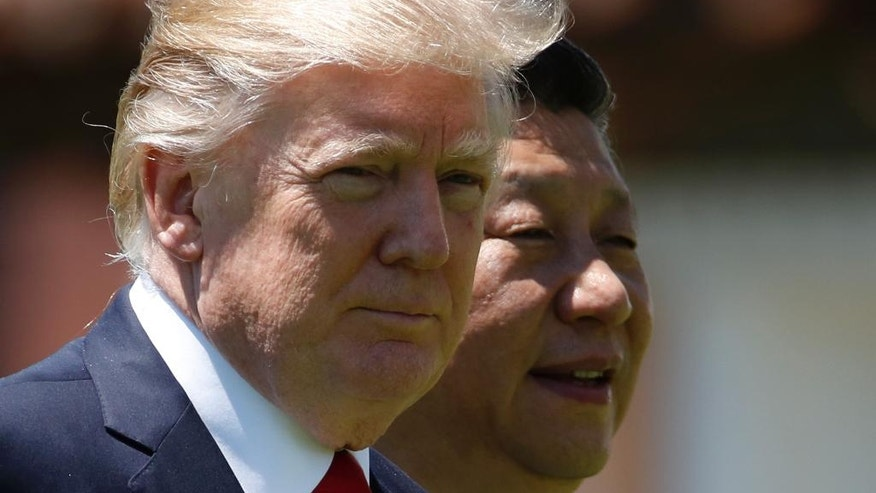 "FILE - In this April 7, 2017, file photo, U.S. President Donald Trump, left, and Chinese President Xi Jinping walk together at Mar-a-Lago in Palm Beach, Fla. Following his meeting with Chinese leader Xi Jinping, U.S. President Donald Trump stepped on a historical land mine when he told the Wall Street Journal that ""Korea actually used to be a part of China."" (AP Photo/Alex Brandon, File)"