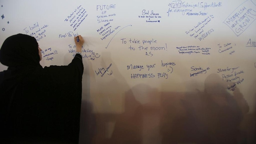In this Wednesday, April 5, 2017, photo, a woman writes a note on a board during the opening day of Step 2017 Conference and Music in Dubai, United Arab Emirates. A mobile app to track school buses, Arabic cooking videos on YouTube and even a portable bideu are finding support from governments in the Gulf as a slide in oil prices forces states to cull cushy public sector jobs and look to entrepreneurs to plug the gap. (AP Photo/Kamran Jebreili)