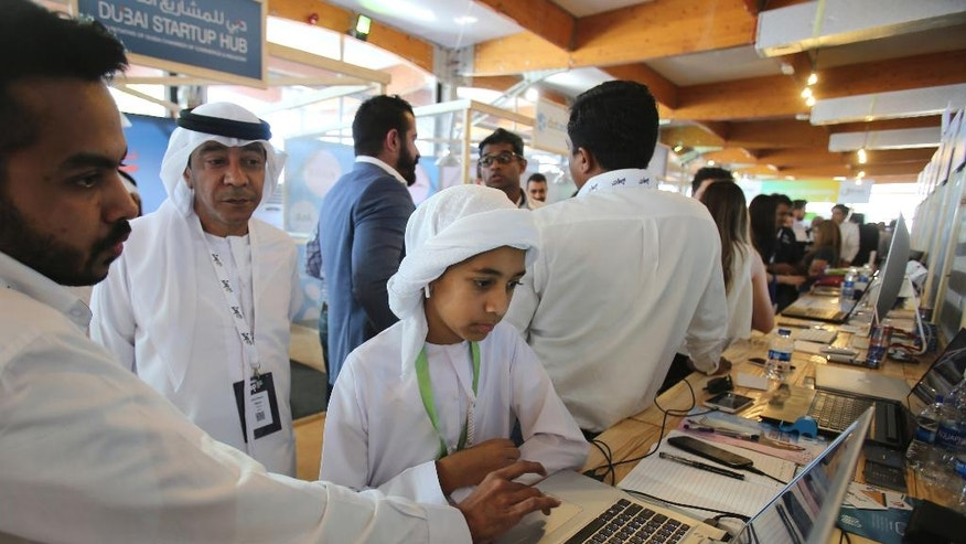 In this Wednesday, April 5, 2017, photo, a young Emirati fan listens to an entrepreneur during the opening day of the Step 2017 Conference and Music in Dubai, United Arab Emirates. A mobile app to track school buses, Arabic cooking videos on YouTube and even a portable bideu are finding support from governments in the Gulf as a slide in oil prices forces states to cull cushy public sector jobs and look to entrepreneurs to plug the gap. (AP Photo/Kamran Jebreili)