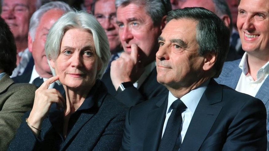 FILE - In this April 9, 2017 file photo, Conservative French presidential candidate Francois Fillon and his wife Penelope attend a campaign meeting in Paris. Conservative candidate Francois Fillon is struggling to keep his chances in the presidential election despite a personal image damaged by corruption allegations. Once a front-runner in the race, Fillon's campaign has been flailing since the investigation began in January. (AP Photo/Thibault Camus, File)