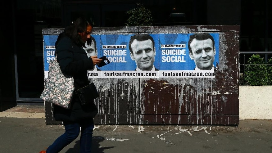 "A woman walks by a presidential campaign poster against Emmanuel Macron reading ""In march to the social suicide, everything except Macron"" displayed in Paris, Thursday, April 20, 2017. Polls suggest Macron has a good chance of coming out on top of Sunday's first round and reaching the May 7 runoff. (AP Photo/Francois Mori)"