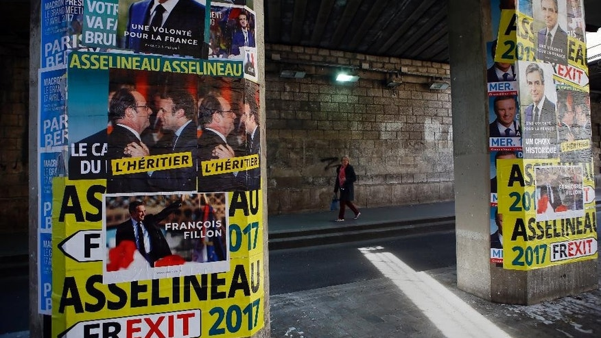 French presidential campaign posters are displayed in Paris, Thursday, April 20, 2017. Polls suggest Macron has a good chance of coming out on top of Sunday's first round and reaching the May 7 runoff.(AP Photo/Francois Mori)