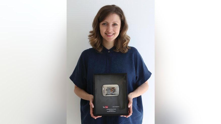 In this Tuesday, April 4, 2017, photo, Alia Adi, founder of YouTube cooking channel Basmaty World, poses with her YouTube award at her studio in Dubai, United Arab Emirates. Alia left Syria soon after the civil war there erupted in 2011 and moved her business to London before deciding on Dubai, where she expanded her channel into a cooking network featuring chefs from across the region making both local and international dishes. (AP Photo/Kamran Jebreili)