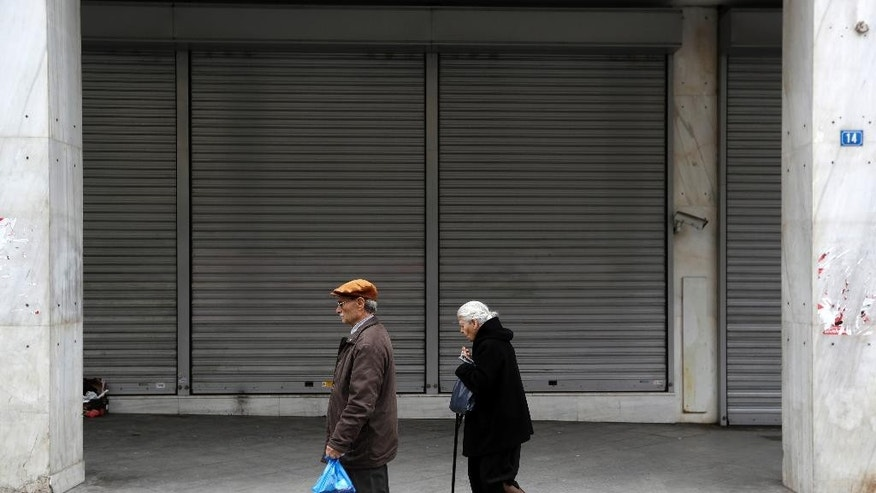 An elderly couple pass a closed bank in Athens, Friday, April 21, 2017. Greece's independent statistics agency says the country has posted a high primary budget surplus in 2016, at 3.9 percent of gross domestic product. (AP Photo/Thanassis Stavrakis)