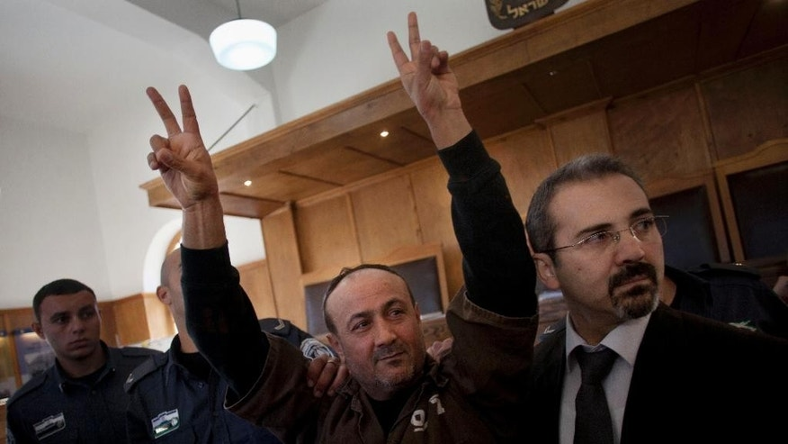 FILE - In this Wednesday, Jan. 25, 2012 file photo, senior Fatah leader Marwan Barghouti makes the victory sign in front of the media during his arrival to testify in a trial at a Jerusalem court.  (AP Photo/Bernat Armangue, File)