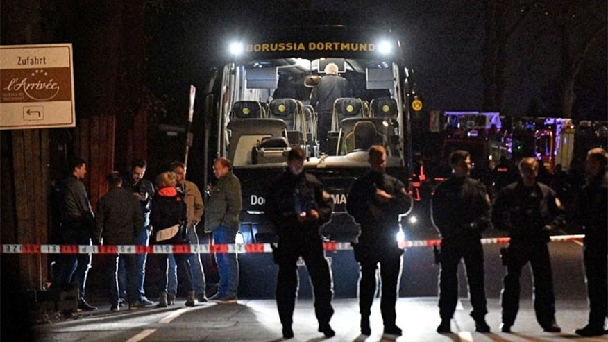 FILE 2017: Authorities stand in front of Dortmund's damaged team bus after explosions which injured two people before the Champions League quarterfinal soccer match between Borussia Dortmund and AS Monaco in Dortmund, western Germany.