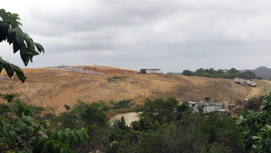 In this April 17, 2017 photo, trucks deposit garbage at a landfill that has been ordered to close by year's end, in Toa Alta, Puerto Rico. Originally built in a sinkhole that forms part of one of the largest and most productive groundwater sources in Puerto Rico, the landfill has since expanded 3 acres (1.2 hectares) outside its boundaries and lacks a system to collect liquefied garbage, control stormwater runoff or monitor the groundwater to ensure it is not contaminating drinking water. (AP Photo/Danica Coto)