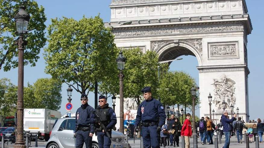 French riot police officers patrol on the Champs Elysees boulevard, with the Arc of Triomphe in background, in Paris, Friday, April 21, 2017. France began picking itself up Friday from another deadly shooting claimed by the Islamic State group, with President Francois Hollande convening the government's security council and his would-be successors in the presidential election campaign treading carefully before voting this weekend. (AP Photo/Christophe Ena)