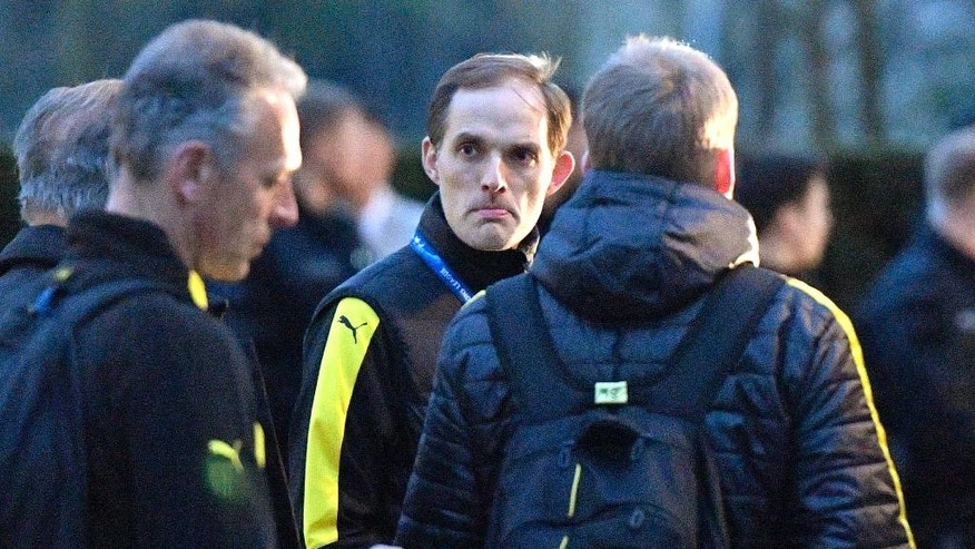 FILE - In this April 11, 2017 file photo Dortmund head coach Thomas Tuchel stands outside the team bus after it was damaged in an explosion before the Champions League quarterfinal soccer match between Borussia Dortmund and AS Monaco in Dortmund, western Germany. (AP Photo/Martin Meissner, file)