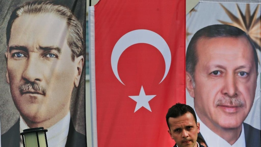 In this Monday, April 3, 2017 photo, a member of security for Erdogan stands guard following a speech at a rally in his hometown Black Sea city of Rize, Turkey, backdropped by banners showing modern Turkey's founder Mustafa Kemal Ataturk, left, and Turkey's current President Recep Tayyip Erdogan. The personality cult that grew around Ataturk has very gradually been fading as current President Recep Tayyip Erdogan, in power since 2003 as alternately prime minister and president, has harked back to the glory days of the height of the Ottoman Empire to whip up patriotic sentiment. (AP Photo/Lefteris Pitarakis)