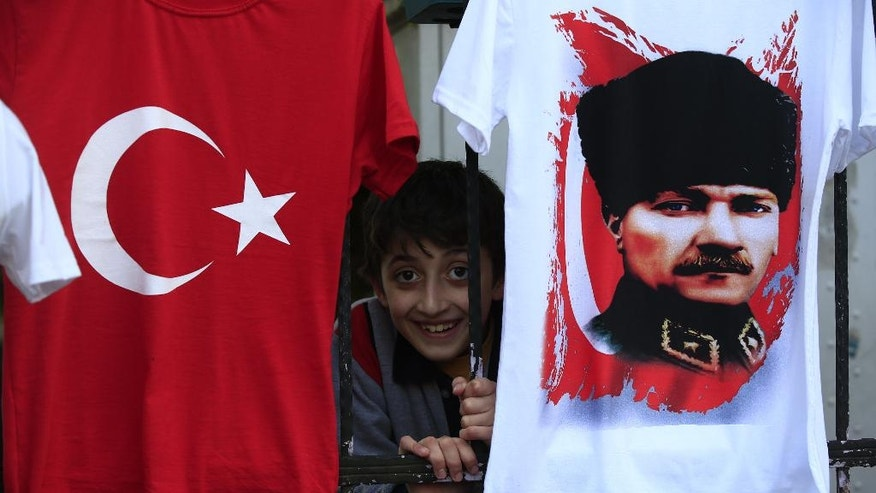 In this Tuesday, April 4, 2017 photo, a child from inside his schoolyard, peers out from behind a fence where t-shirts with the Turkish flag, and the picture of modern Turkey's founder Mustafa Kemal Ataturk, are offered for sale in the Black Sea city of Rize, Turkey. The eroding personality cult of Ataturk suffered its biggest blow yet when Turkey voted April 16 to expand the powers of the presidency, undercutting the parliamentary system that Ataturk imposed nearly a century ago. (AP Photo/Lefteris Pitarakis)