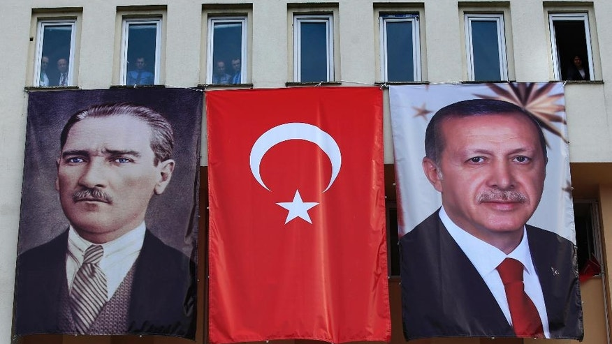 In this Monday, April 3, 2017 photo, banners showing modern Turkey's founder Mustafa Kemal Ataturk, left, and Turkey's current President Recep Tayyip Erdogan, right, decorate a building as people watch Erdogan's speech, during a rally for the upcoming referendum, in his hometown city of Rize, in the Black Sea region, Turkey. The personality cult that grew around Ataturk has very gradually been fading as current President Recep Tayyip Erdogan, in power since 2003 as alternately prime minister and president, has harked back to the glory days of the height of the Ottoman Empire to whip up patriotic sentiment. (AP Photo/Lefteris Pitarakis)