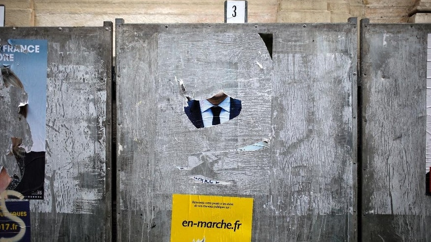 A torn poster of independent centrist presidential candidate Emmanuel Macron is displayed in front of a polling station in Lyon, central France, Saturday, April 22, 2017. The two-round presidential election will take place on April 23 and May 7. (AP Photo/Laurent Cipriani)