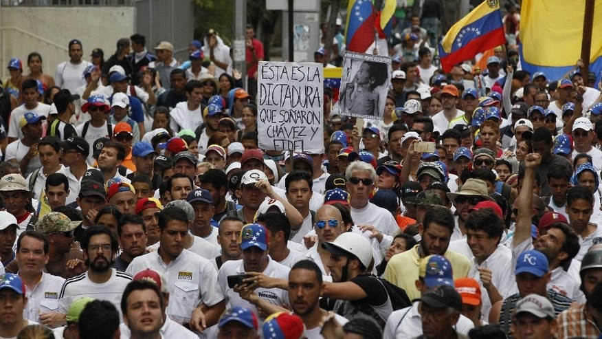 "People protest in homage to the at least 20 people killed in unrest generated after the nation's Supreme Court stripped congress of its last powers, a decision it later reversed, during a silent march to the Venezuelan Episcopal Conference in Caracas, Venezuela, Saturday, April 22, 2017. The sign reads in Spanish ""This is the dictatorship that Chavez and Fidel dreamed of."" In the front of the picture are, from left, lawmaker Tomas Guanipa, lawmaker Miguel Pizarro, lawmaker Jose Manuel Olivares, Miranda state Governor and opposition leader Henrique Capriles, and lawmaker Juan Requesens. (AP Photo/Ariana Cubillos)"