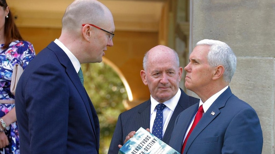 U.S. Vice President Mike Pence, right, receives the gift of a book called Rendezvous with Destiny by Michael Fullilove, left, as Australian Governor General Peter Cosgrove looks on during a lunch reception for Australian and U.S. military servicemen and women at Admiralty House in Sydney, Saturday, April 22, 2017. (Jason Reed/Pool Photo via AP)