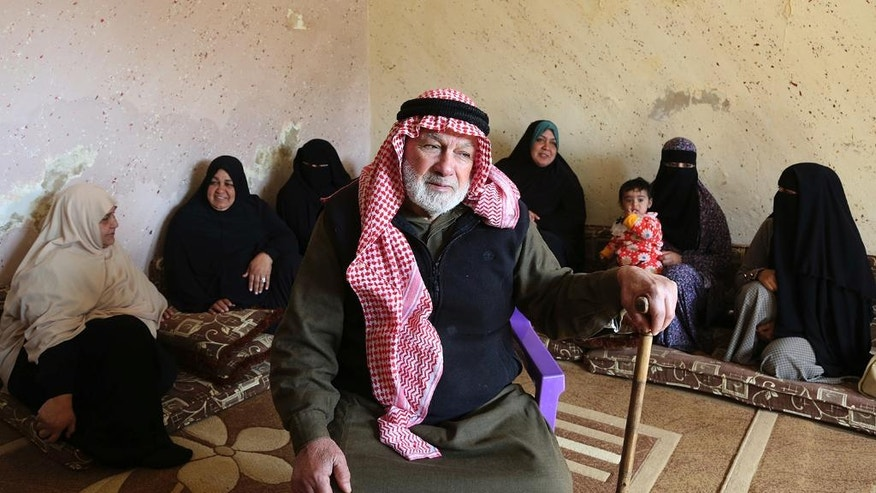 In this photo taken Wednesday, Feb. 8, 2017, Palestinian refugee Abdullah Abu Massoud, 77, poses for a photo in his living room. Members of his expanded clan which includes seven children, 46 grandchildren and dozens of great-grandchildren, are seen in the background. The plight of Palestinians uprooted by Israeli-Arab wars now spans five generations, one of the longest-running refugee crises. As the second wave of displacement hits the half-century mark, a solution for millions of refugees and their descendants is more distant than ever. (AP Photo/Raad Adayleh)