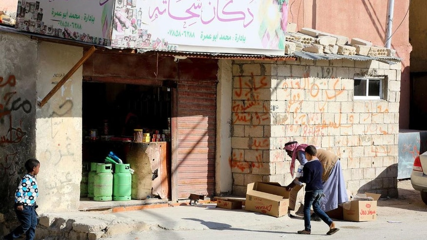 This photo taken Wednesday, Feb. 8, 2017, shows a resident of the Palestinian refugee camp of Jerash in northern Jordan move cartons outside a small grocery. The plight of Palestinians uprooted by Israeli-Arab wars now spans five generations, one of the longest-running refugee crises. As the second wave of displacement hits the half-century mark, a solution for millions of refugees and their descendants is more distant than ever. (AP Photo/Raad Adayleh)