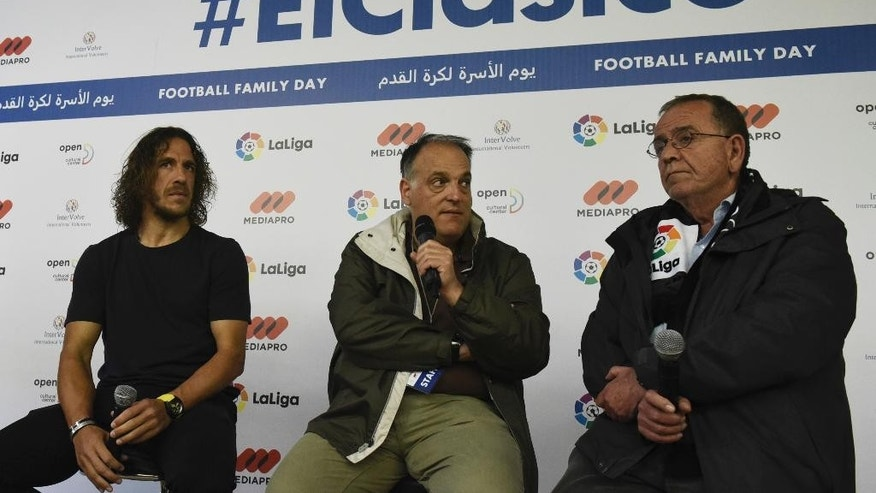 "Retired Spanish player and La Liga ambassador Carles Puyol, left, La Liga President Xavier Tebas, center, and Greece's Migration Minister, Yannis Mouzalas attend a news briefing in Thessaloniki, Greece, Sunday, April 23, 2017. About 1,000 refugees residing in northern Greece attended an event in the framework of ""Football Family Day"" during which they watched a live broadcasting of Spanish first division soccer match between Barcelona and Real Madrid on two giant screens. (AP Photo/Giannis Papanikos)"