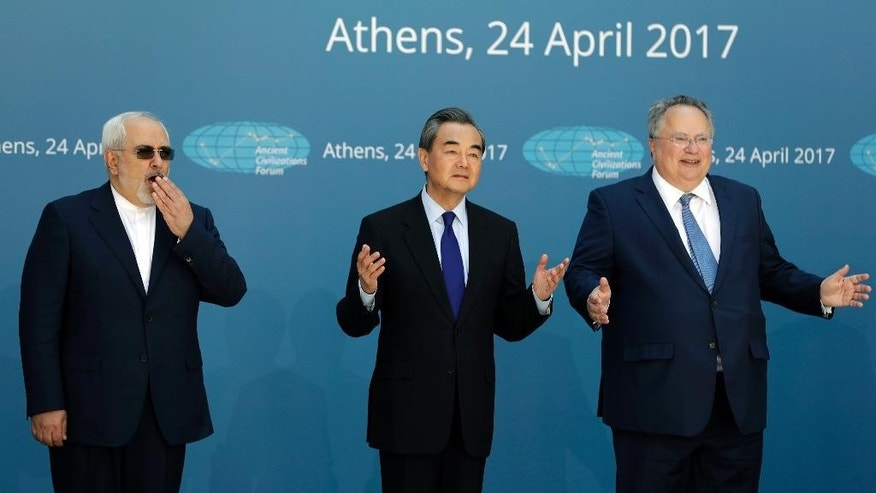 "Greek Foreign Minister Nikos Kotzias, right, and his Iranian counterpart Mohammad Javad Zarif, left, and Chinese Foreign Minister Wang Yi gesture as they pose for the photographers as they attend the ""Ancient Civilizations Forum"" (ACForum) at Zappeio Conference Hall in Athens, Monday, April 24, 2017. Foreign Ministers and top officials from various countries attended the forum being held in the Greek capital. (AP Photo/Thanassis Stavrakis)"