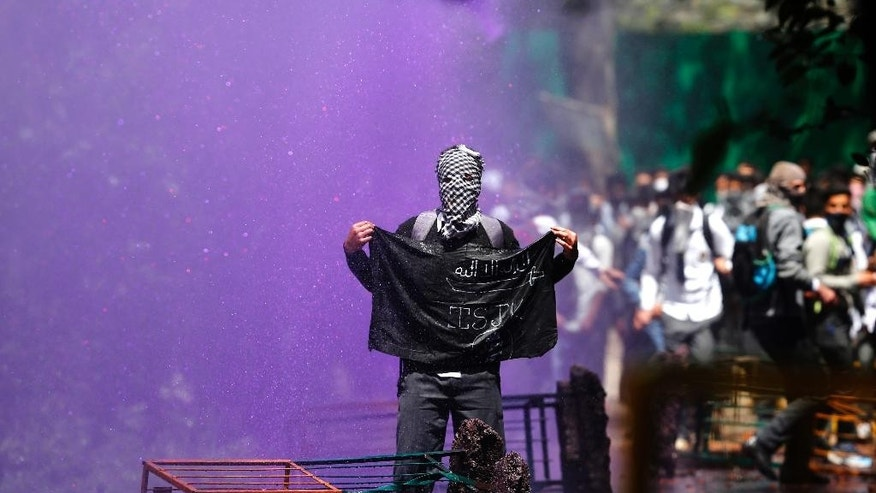 A Kashmiri student holds a black flag as Indian police use colored water to disperse them as they clash in Srinagar, Indian controlled Kashmir, Monday, April 24, 2017. Tensions between Kashmiri students and Indian law enforcement have escalated since April 15, when government forces raided a college in Pulwama, about 30 kilometers (19 miles) south of Srinagar, to scare anti-India activists. (AP Photo/Mukhtar Khan)