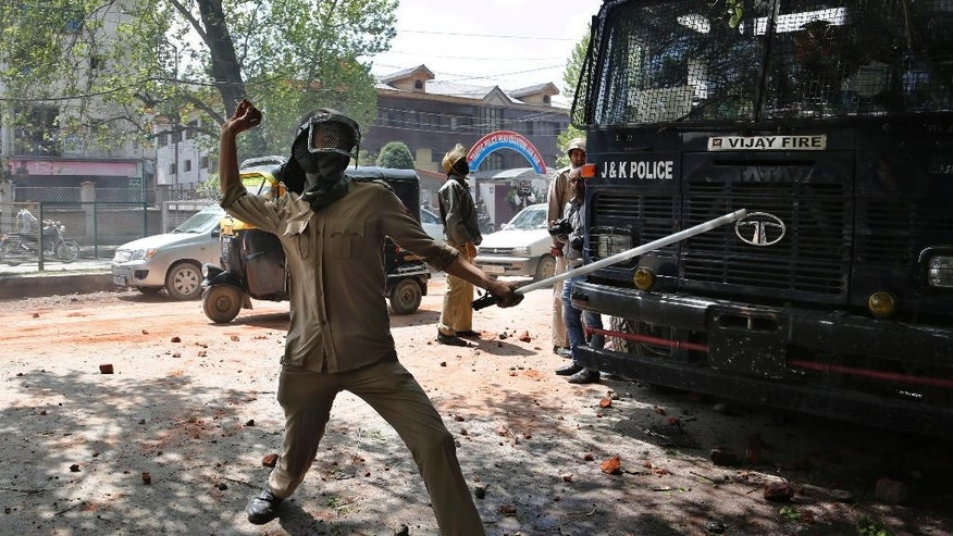 An Indian police man throws stones at protesters supporting students as they clash in Srinagar, Indian controlled Kashmir, Monday, April 24, 2017. Tensions between Kashmiri students and Indian law enforcement have escalated since April 15, when government forces raided a college in Pulwama, about 30 kilometers (19 miles) south of Srinagar, to scare anti-India activists. (AP Photo/Mukhtar Khan)
