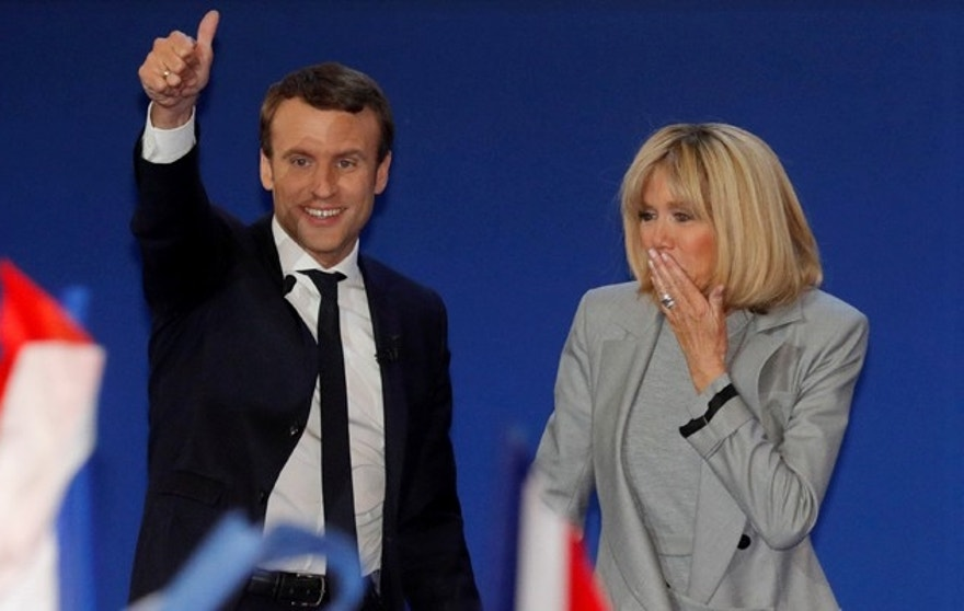 Emmanuel Macron, head of the political movement En Marche !, or Onwards !, and candidate for the 2017 French presidential election, arrives on stage with his wife Brigitte Trogneux to deliver a speech at the Parc des Expositions hall in Paris after early results in the first round of 2017 French presidential election, France, April 23, 2017.   REUTERS/Philippe Wojazer - RTS13LDJ