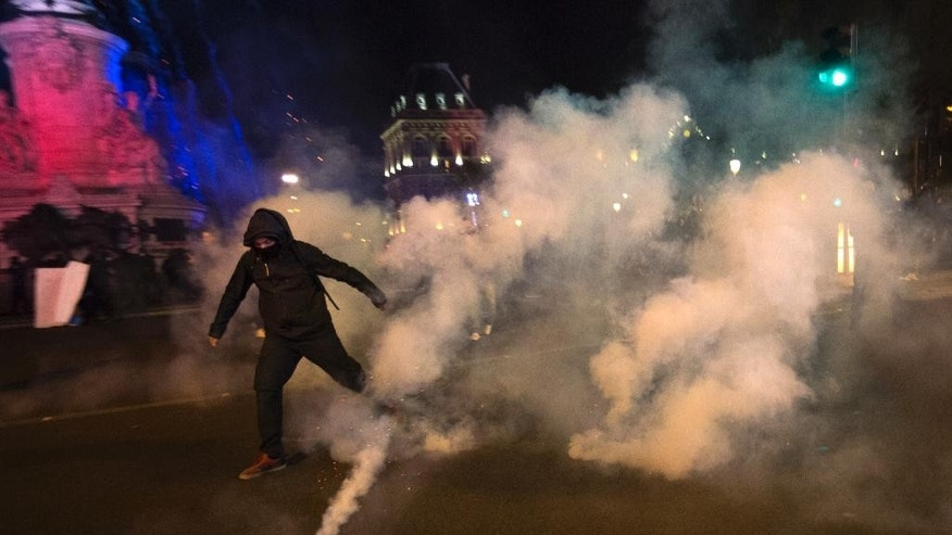 "A demonstrator runs away from tear gas during clashes with police in Paris, Sunday, April 23, 2017. Protesters angry that far-right leader Marine Le Pen is advancing the French presidential runoff are scuffling with police in Paris. Crowds of young people, some from anarchist and ""anti-fascist"" groups, gathered on the Place de la Bastille in eastern Paris as results were coming in from Sunday's first-round vote. (AP Photo/Emilio Morenatti)"